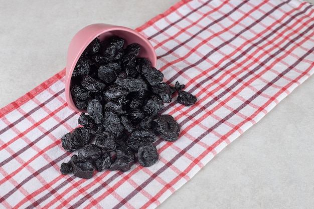 Suszone czarne śliwki w naczyniu ceramicznym.