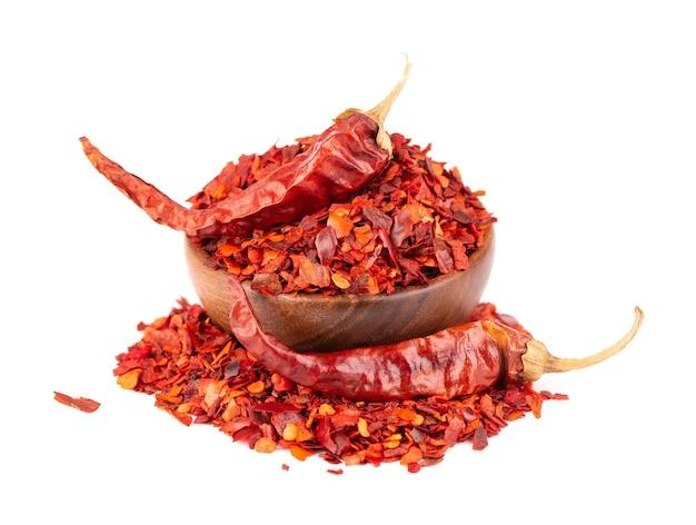 Suszone czerwone chili płatki w drewnianej misce, na białym tle. posiekany pieprz cayenne chilli. przyprawy i zioła.