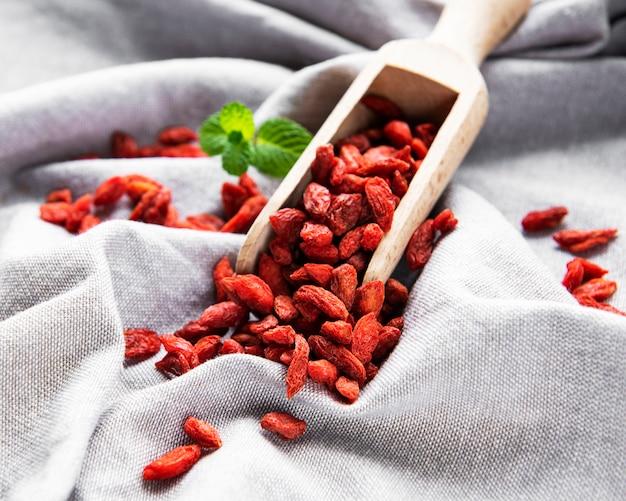 Suszone czerwone jagody goji dla zdrowej diety na tkaninowym tle