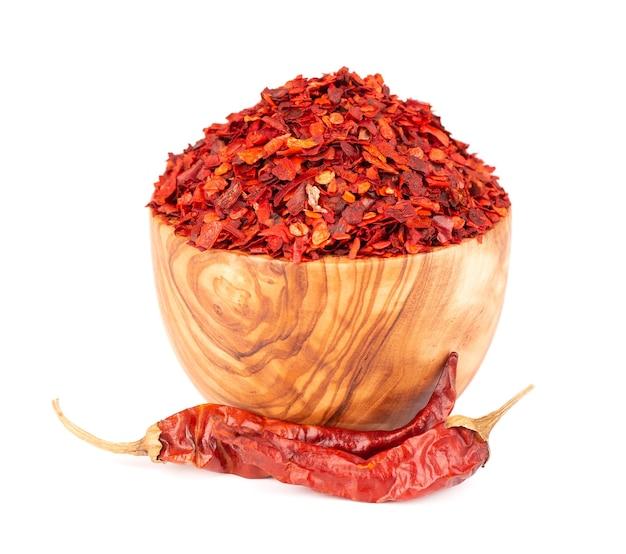 Suszone czerwone płatki chili w oliwnej misce, na białym tle. posiekany pieprz cayenne chilli. przyprawy i zioła.