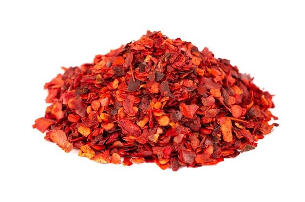 Suszone czerwone płatki chili z nasionami, na białym tle. posiekany pieprz cayenne chilli. przyprawy i zioła.
