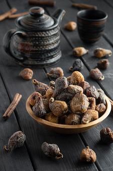 Suszone figi w misce, na ciemnej powierzchni drewna, czajnik na tle