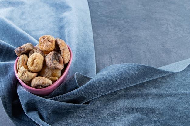 Suszone figi w misce na kawałku tkaniny na marmurowej powierzchni