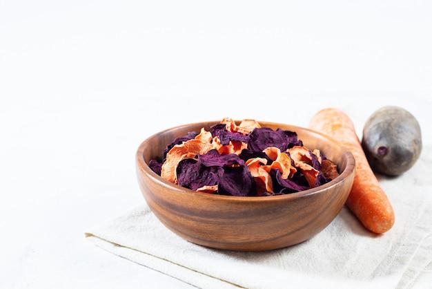 Suszone frytki z marchwi i buraków w drewnianej misce i surowe marchewki, buraki na białym tle betonu.