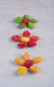 Suszone galaretki owocowe multicolor na białym tle na powierzchni betonu.