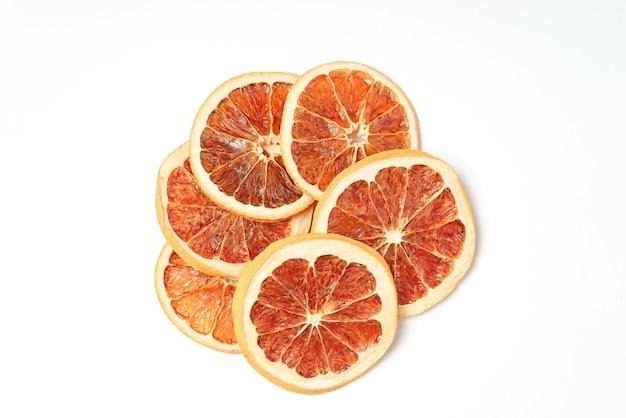 Suszone grejpfruty na białym tle, pomarańczowy plasterki owoców cytrusowych.
