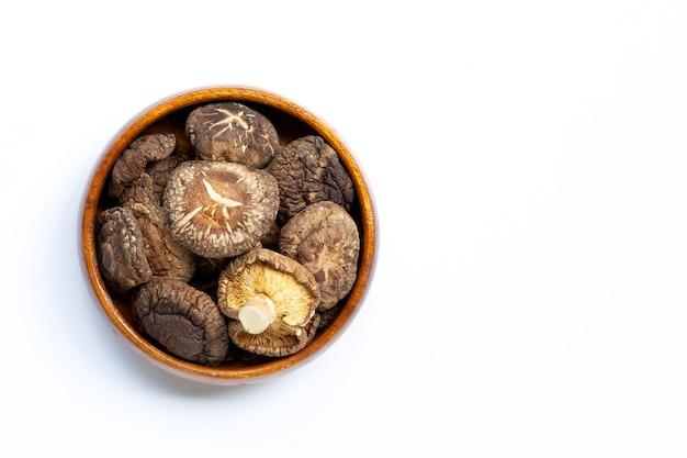 Suszone grzyby shiitake w drewnianej misce.