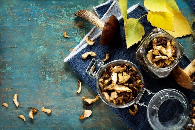 Suszone grzyby w słoikach i jesienne liście
