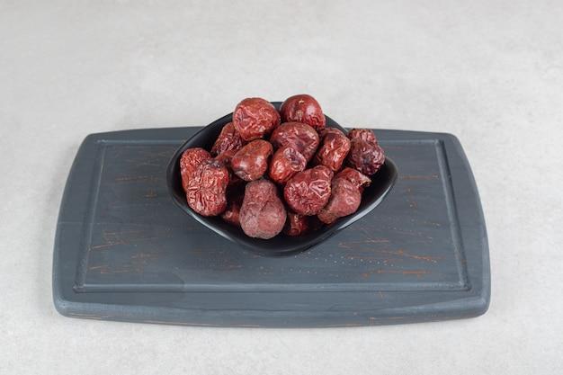Suszone indyjskie jagody jujube na drewnianym talerzu.