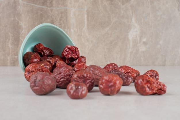 Suszone indyjskie jagody jujube w ceramicznej filiżance.