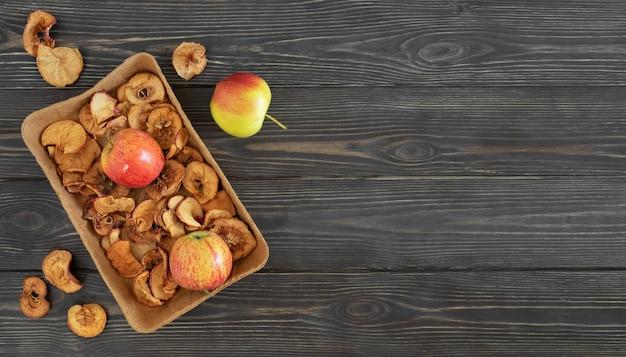 Suszone jabłka i dojrzałe jabłka na ciemnym drewnianym stole