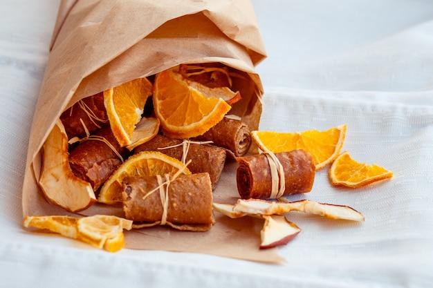Suszone jabłka i pomarańcze rozrzucone na serwetce