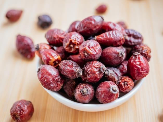 Suszone jagody dzikiej róży lub róży canina. suszone owoce słodko-brier lub róży na białej misce na podłoże drewniane. koncepcja zdrowych i ziołowych. selektywna ostrość