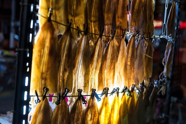 Suszone kalmary wiszące do kupienia na nocnym targu w hua hin. słynne tajskie jedzenie uliczne.