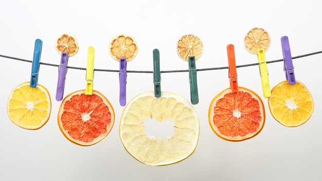 Suszone kawałki owoców cytrusowych wiszą na spinaczach do bielizny