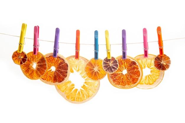 Suszone kawałki różnych owoców cytrusowych wiszą na kolorowych spinaczach do bielizny na białym tle
