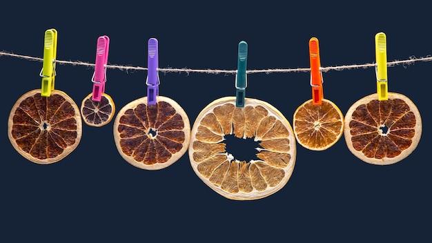Suszone kawałki różnych owoców cytrusowych wiszą na kolorowych spinaczach do bielizny na niebieskim tle