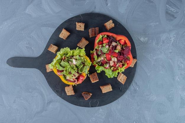 Suszone kawałki skórki wokół kawałków papryki wypełnionej porcjami sałatki na marmurowym stole.