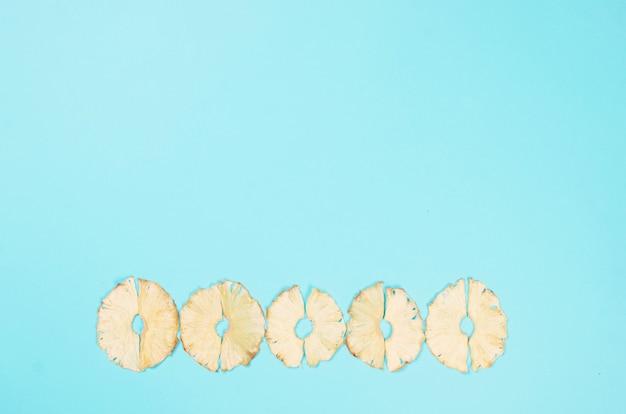 Suszone kliny ananasa rozrzucone na niebieskim tle. chipsy owocowe. koncepcja zdrowego odżywiania, przekąska, bez cukru. widok z góry, kopia przestrzeń.