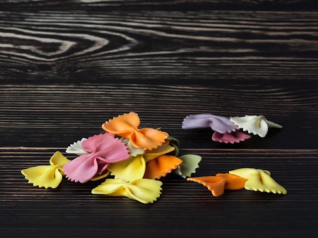 Suszone kolorowe włoskie makarony farfalle lub łuki na ciemnym tle drewnianych. z miejscem na kopię