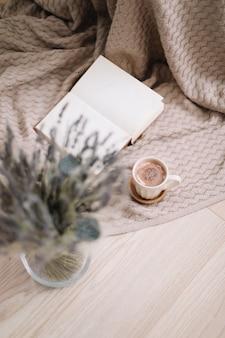 Suszone kwiaty i filiżanka cappuccino z książką na drewnianym tle widok z góry