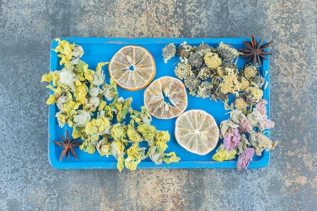 Suszone kwiaty i plasterki cytryny na niebieskim talerzu.