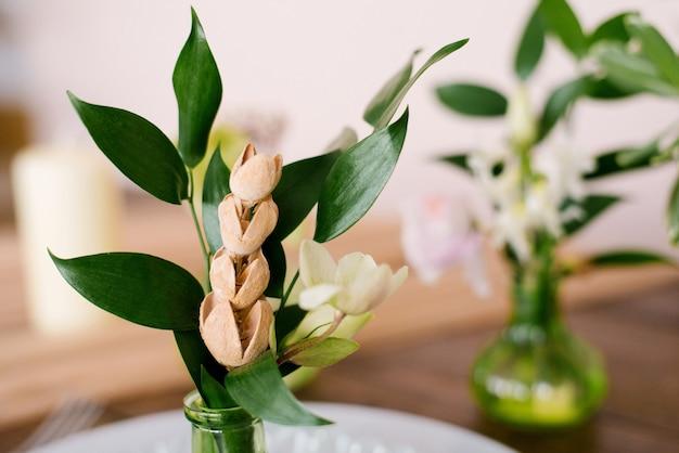 Suszone kwiaty i zielone liście w szklanym zielonym wazonie w wystroju wnętrza lub na stole