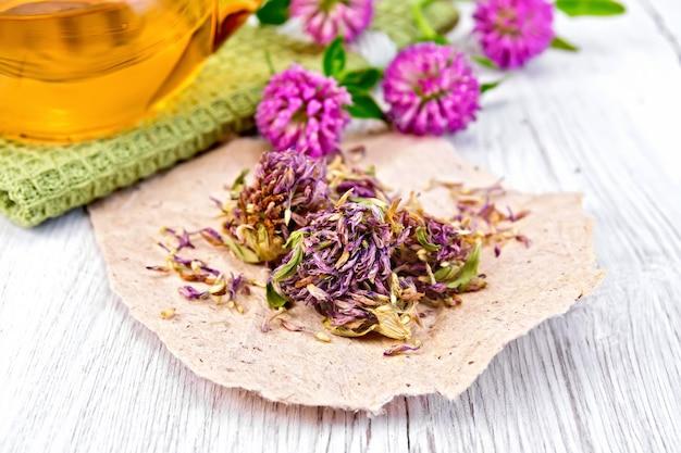 Suszone kwiaty koniczyny na papierze, herbata w szklanym imbryku na serwetce, świeże kwiaty koniczyny na tle lekkich desek
