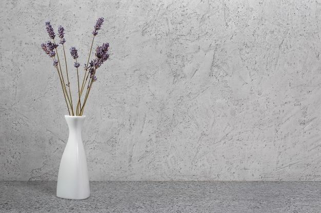 Suszone kwiaty lawendy w białym wazonie na powierzchni kamienia. wewnętrzna kompozycja kwiatowa.
