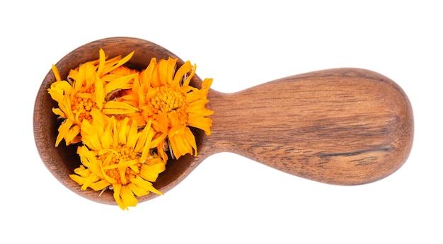 Suszone kwiaty nagietka w drewnianą łyżką, na białym tle. płatki nagietka lekarskiego. zioła medyczne. widok z góry.