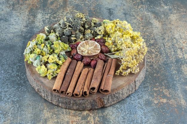 Suszone kwiaty, owoce dzikiej róży i cynamon na drewnianym kawałku.
