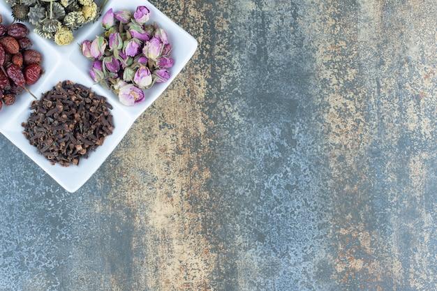Suszone kwiaty, owoce dzikiej róży i goździki na białym talerzu.