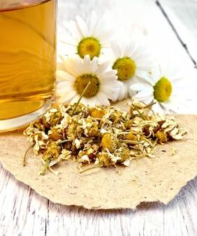 Suszone kwiaty rumianku na papierze, herbata w szklanym kubku, świeże kwiaty stokrotki na tle jasnej drewnianej deski