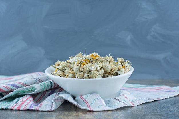 Suszone kwiaty rumianku w białej misce.