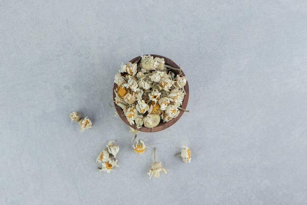 Suszone kwiaty rumianku w drewnianej misce.