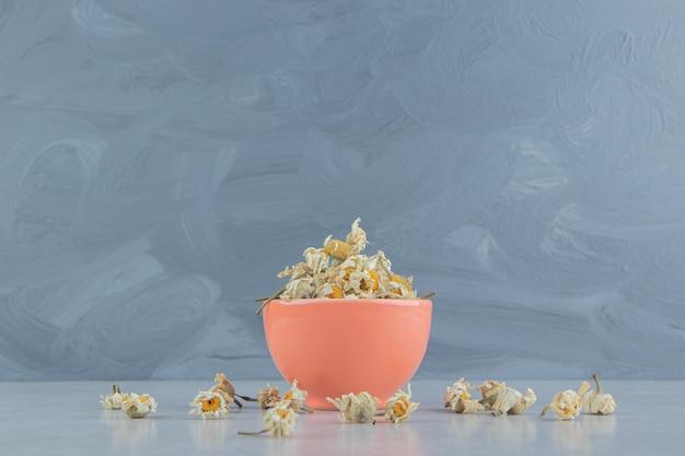 Suszone kwiaty rumianku w misce pomarańczowy.