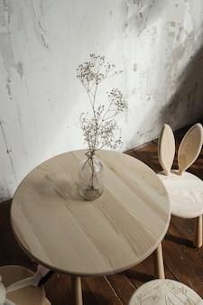 Suszone kwiaty w szkle na drewnianym stole