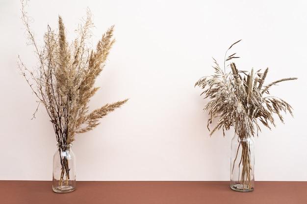 Suszone kwiaty w wazonach na jasnoróżowym i brązowym tle.
