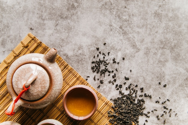 Suszone liście herbaty z czajnikiem i miską na podkładce na betonowym tle