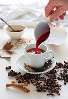 Suszone liście hibiskusa na herbatę lub napary, laski cynamonu i brązowy cukier