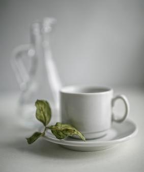 Suszone liście jabłoni, leżące na spodku do herbaty obok karafki