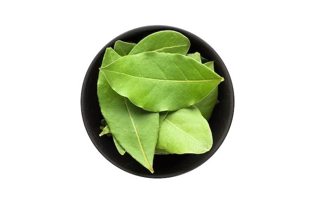 Suszone liście laurowe w glinianej misce na białym tle. przyprawa lub przyprawa widok z góry