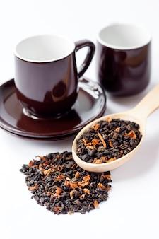 Suszone liście zielonej herbaty z płatkami kwiatów w drewnianej łyżce i filiżance ze spodkiem