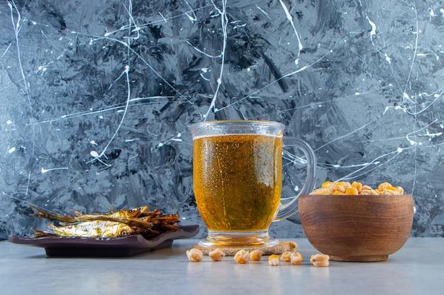 Suszone małe solone szproty na półmisku obok szklanki do piwa i ciecierzycy, na marmurowym tle.