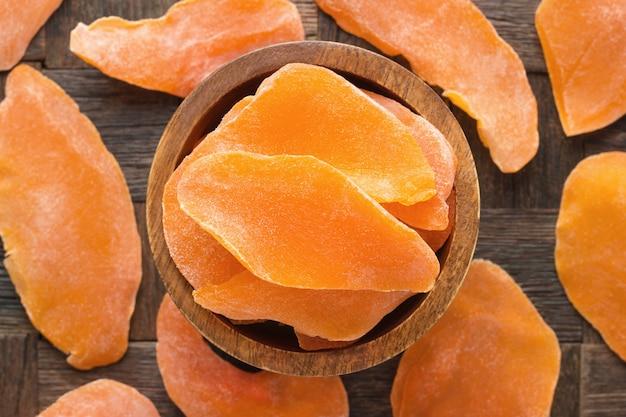 Suszone mango z cukrem w drewnianej misce