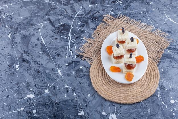 Suszone morele i ser na talerzu na trójnogu, na niebiesko.