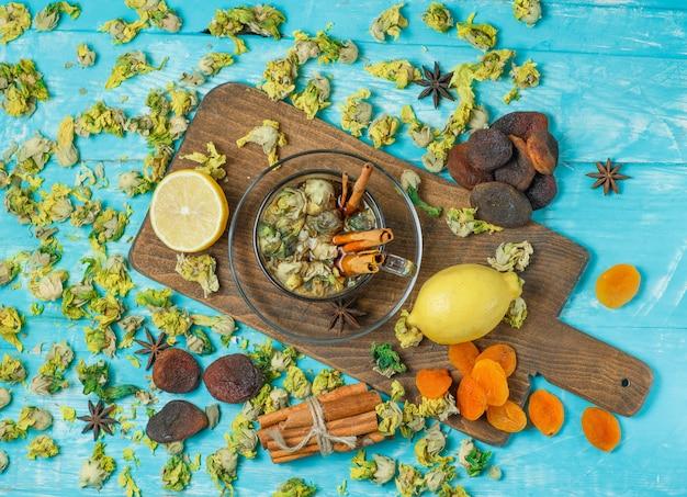 Suszone morele z przyprawami, herbatą, cytryną, ziołami na niebiesko i deską do krojenia.