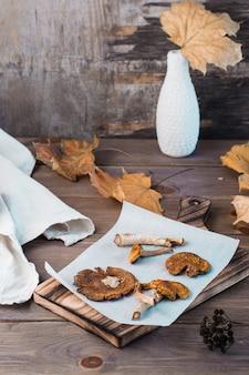 Suszone muchomory na pergaminie na drewnianym stole. mikrodozowanie i medycyna alternatywna. widok pionowy