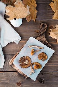 Suszone muchomory na pergaminie na drewnianym stole. mikrodozowanie i medycyna alternatywna. widok z góry i z pionu