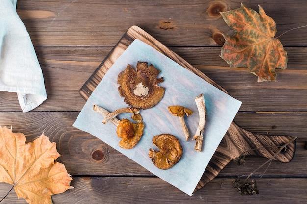Suszone muchomory na pergaminie na drewnianym stole. mikrodozowanie i medycyna alternatywna. widok z góry
